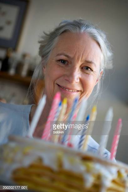 Senior woman holding up birthday cake, smiling, portrait, close-up