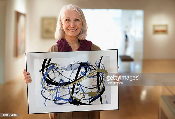 senior woman holding up designs - konstmuseum bildbanksfoton och bilder