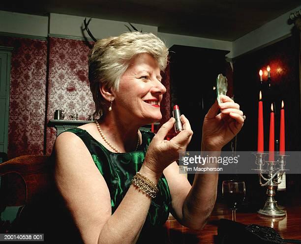 Senior woman holding up mirror and lipstick, formal attire