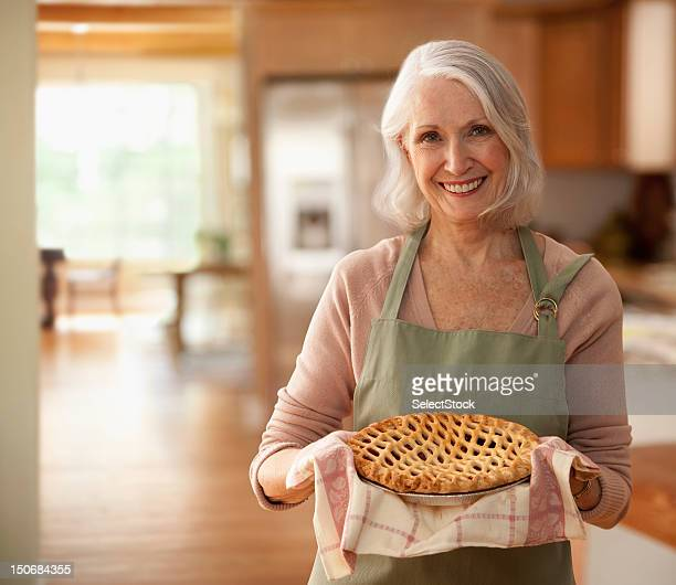 Senior woman holding up pie