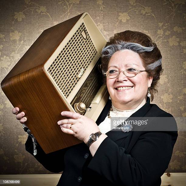 Senior Woman Holding Vintage Radio on Shoulder