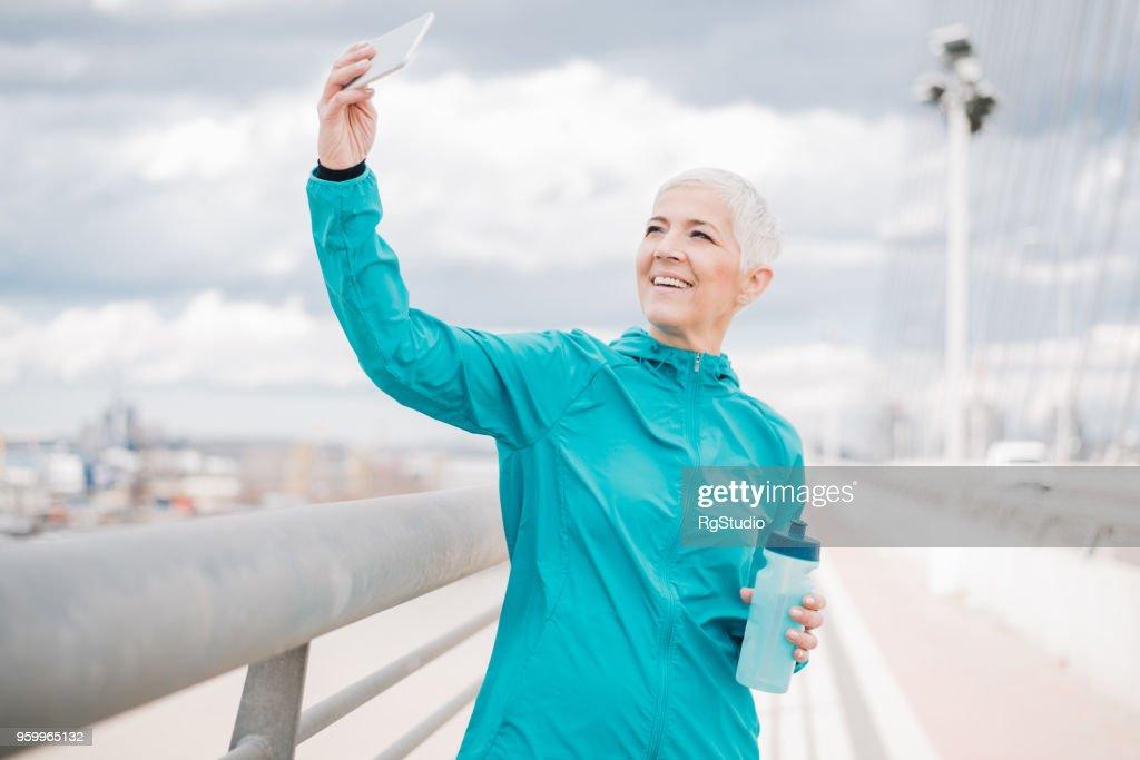 Ältere Frau hält die Flasche Wasser und ein Selbstporträt zu machen : Stock-Foto