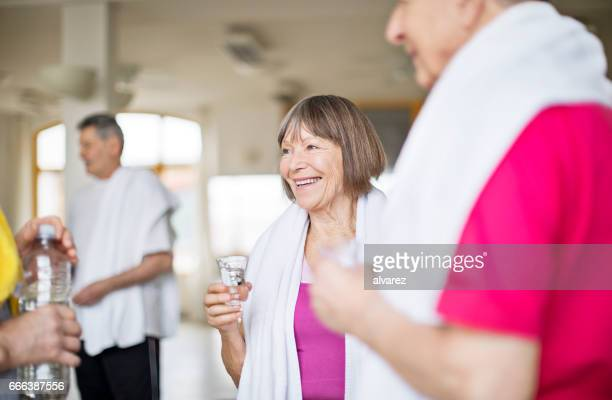 Senior woman holding water glass by males in gym