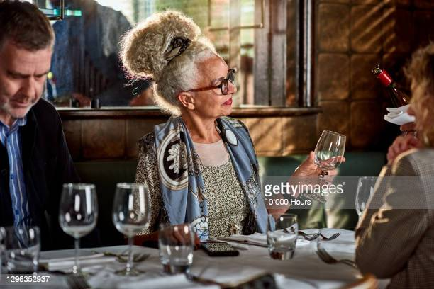 senior woman holding wine glass in restaurant - elegance stock pictures, royalty-free photos & images