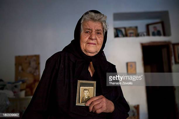 Senior woman hold's a photograph of her dead husband in her house on 3 August 2013 in Mani, Greece.
