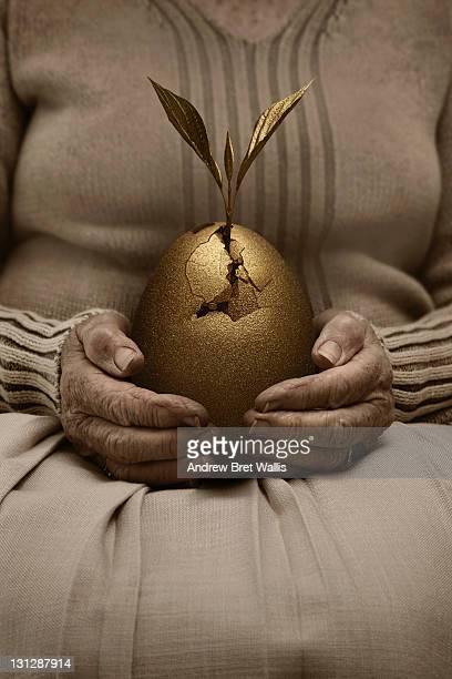 Senior woman holds hatching golden egg in her lap