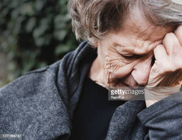 senior woman holds her head as she is stricken by grief - blame stock pictures, royalty-free photos & images