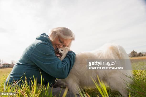 Senior Woman Hugging American Eskimo Dog Outdoors