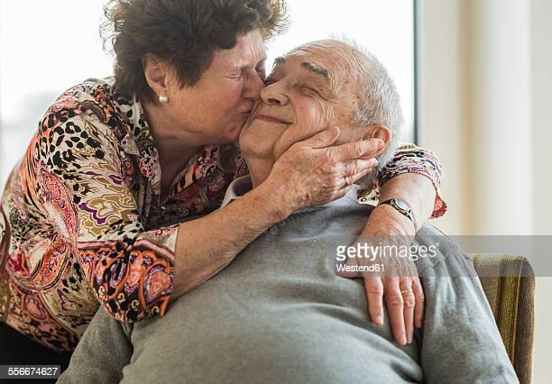 Senior woman hugging and kissing his husband