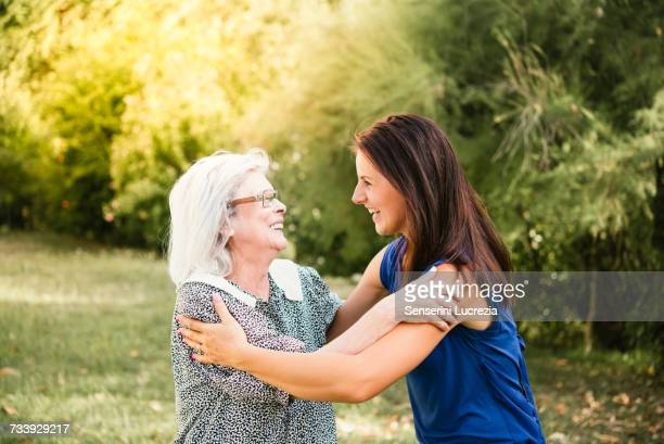 senior woman, hugging granddaughter, outdoors - family reunion stock pictures, royalty-free photos & images