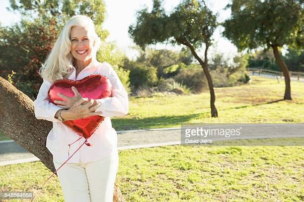 Senior woman hugging red heart-shaped balloon, Hahn Park, Los Angeles, California, USA