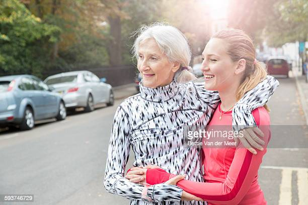 Senior woman hugs daughter after run, cityscape.