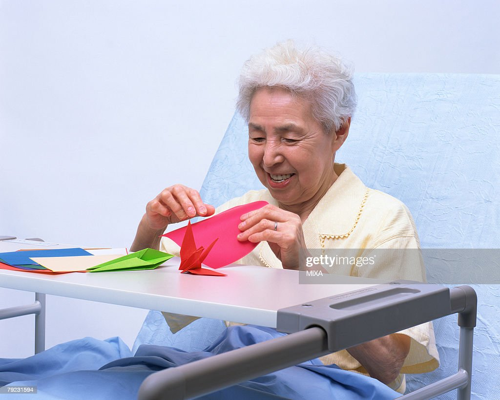 A senior woman in a bed playing with origami : Stock Photo