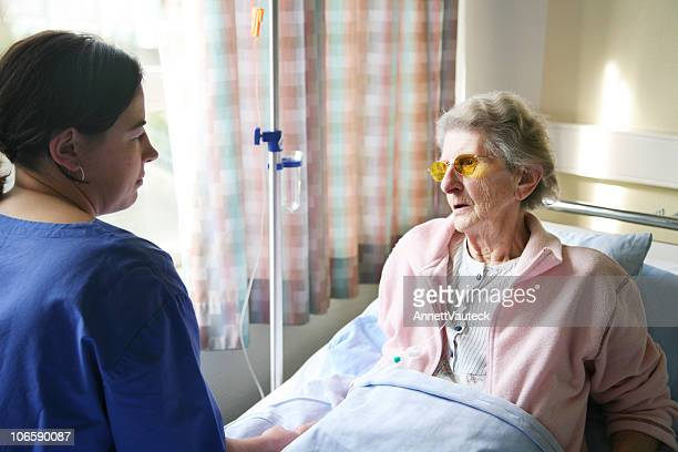 Senior woman in a hospital bed, talking to a nurse