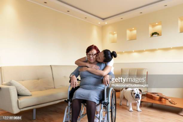 senior woman in a wheelchair is receiving treatment by her careful daughter. glad to have the caregiver by my side. - chinese bulldog stock pictures, royalty-free photos & images