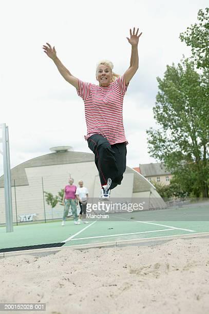 senior woman in air performing long jump - extra long ストックフォトと画像