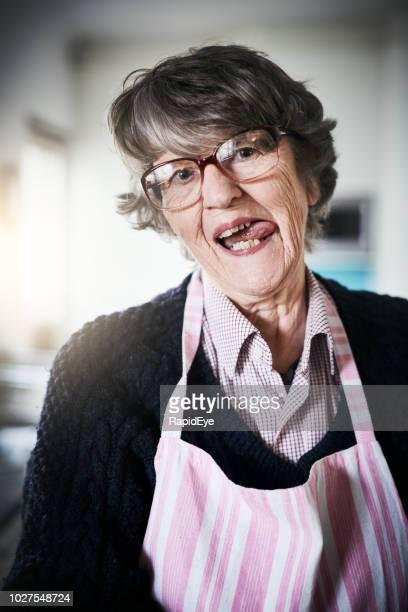mulher sênior no avental lambe os lábios, sorrindo - lambendo os lábios - fotografias e filmes do acervo