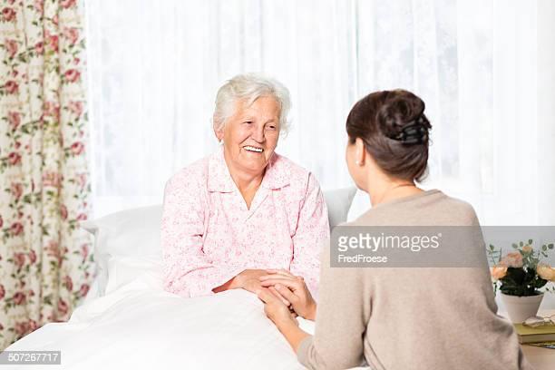 Senior Frau im Bett zu Hause mit Altenpfleger