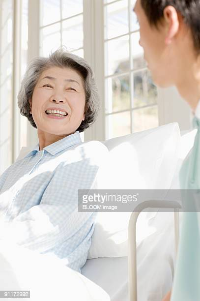 Senior woman in bed talking with male care worker
