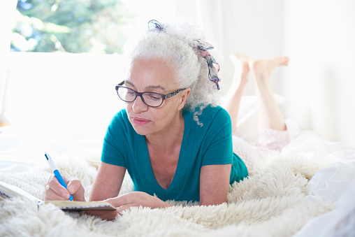 senior woman in bed writing in diary - gettyimageskorea