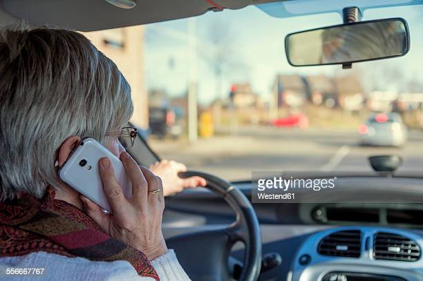 Senior woman in car on cell phone