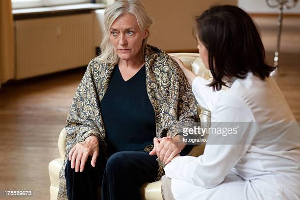 senior Frau bei uns zu Hause kommt Aufmerksamkeit von Ärztin