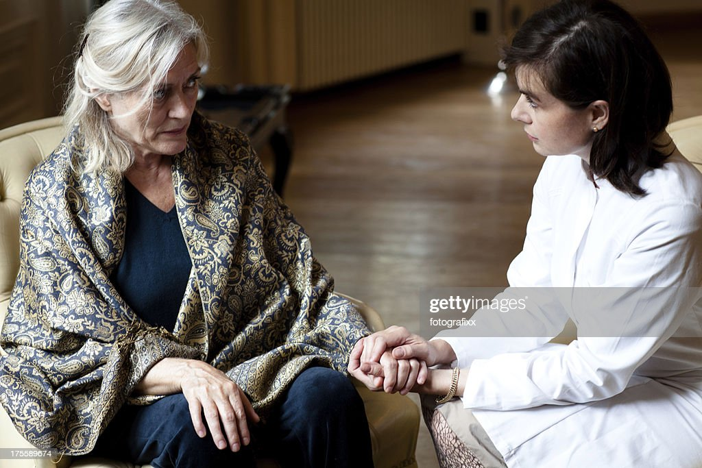 senior woman in care home gets attention from female doctor : Stock Photo