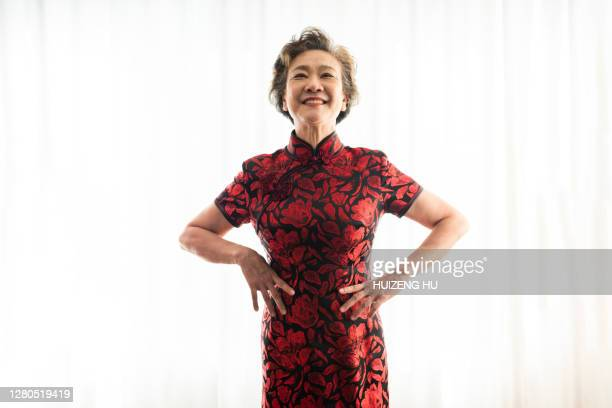 senior woman in cheongsam.  happy senior woman smiling at camera. - arms akimbo stock pictures, royalty-free photos & images