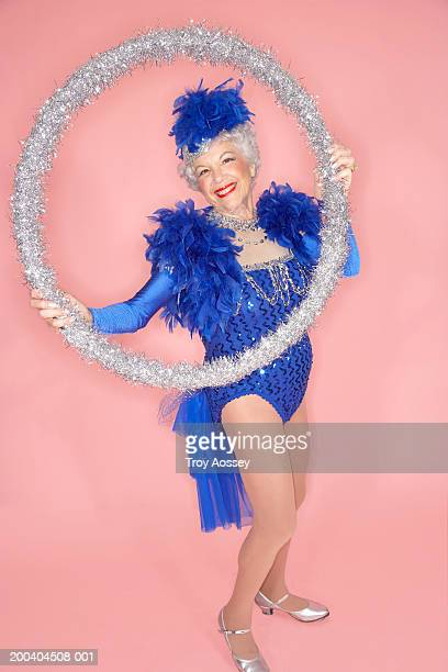 Senior woman in costume holding large hoop, smiling, portrait