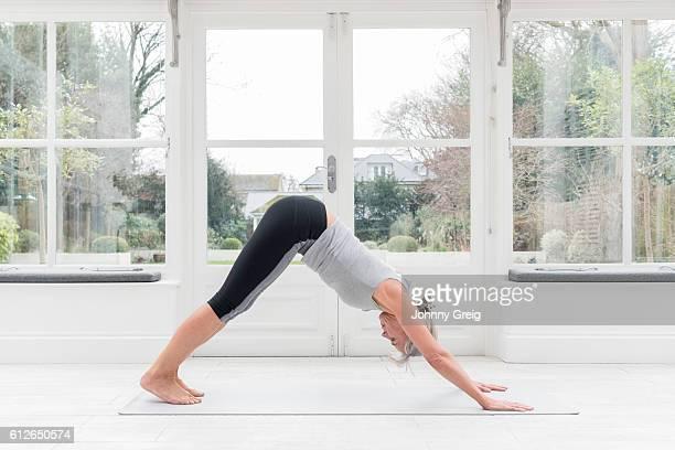 Senior woman in downward dog yoga position