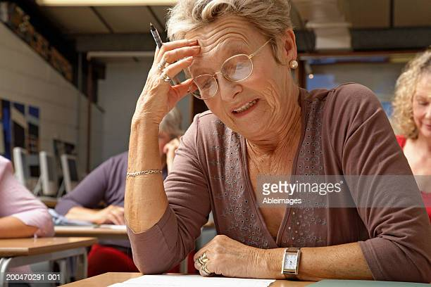 Senior woman in examination hall, staring at paper, hand to head