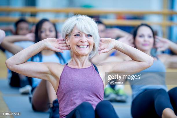 senior woman in fitness class doing a sit-up and smiling stock photo - 50 59 years stock pictures, royalty-free photos & images