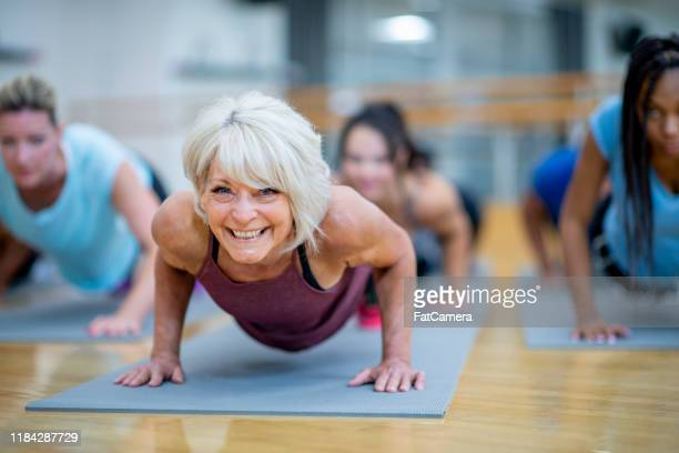 senior woman in fitness class in a plank pose smiling stock photo - 50 54 years stock pictures, royalty-free photos & images