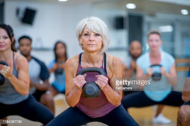 senior woman in fitness class using a kettlebell stock photo - 50 54 years stock pictures, royalty-free photos & images