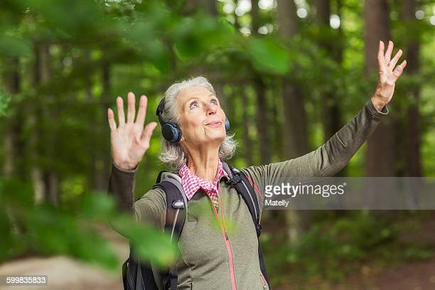 Senior woman in forest, wearing headphones, arms raised