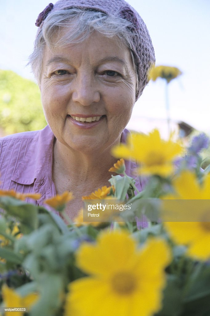 Senior woman in front of flowers, close up : Stock Photo