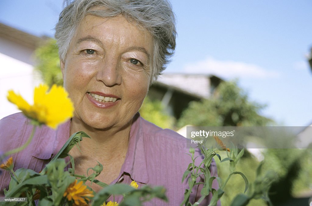 Senior woman in front of flowers, low angle view : Stock Photo
