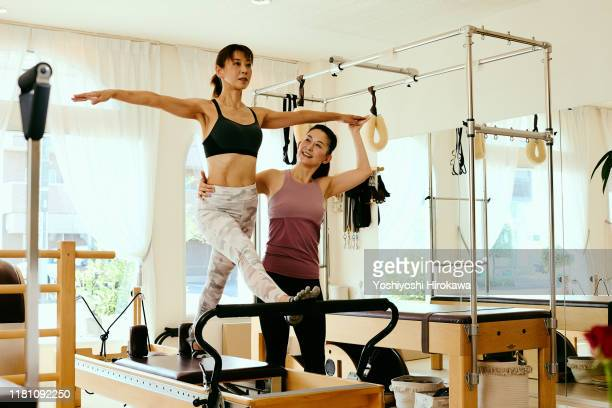 senior woman in front split on pilates reformer during class while female trainer adjusts form - healthcare stock pictures, royalty-free photos & images