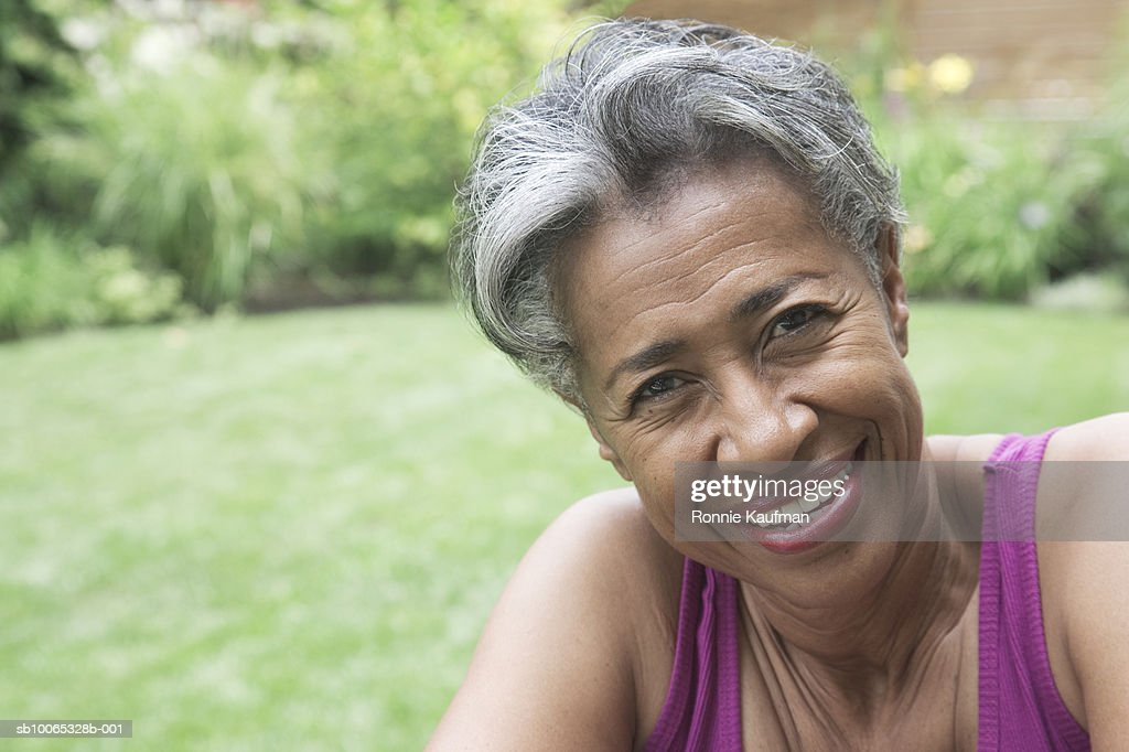 Senior woman in garden, smiling, portrait, close-up : Foto stock