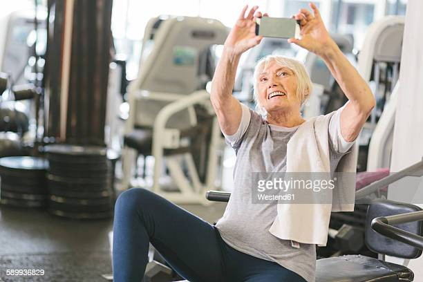 Senior woman in gym taking a selfie