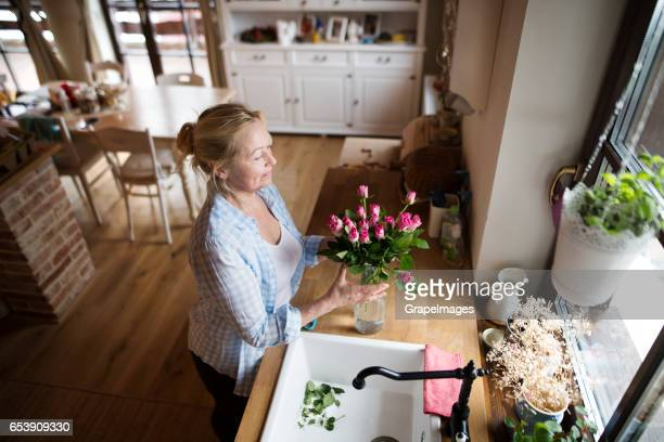Senior woman in her kitchen arranging roses in vase