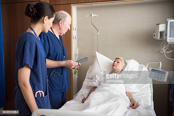 Senior woman in hospital bed listening to doctor and nurse