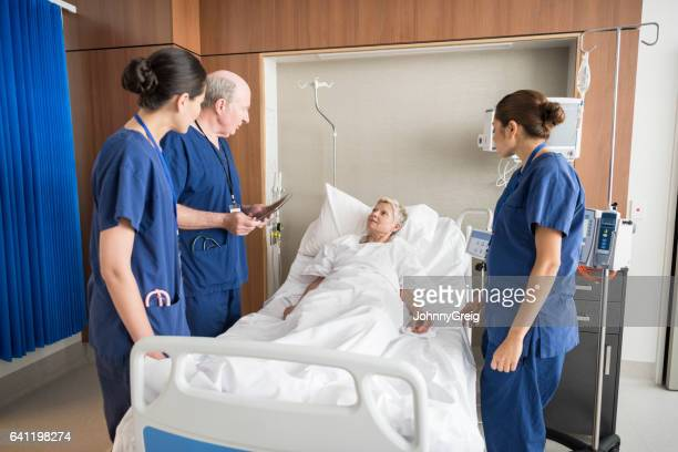 Senior woman in hospital bed listening to doctor and nurses
