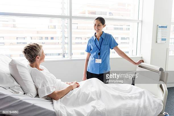 Senior woman in hospital bed talking to Asian nurse, smiling