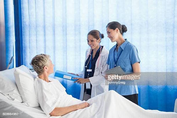 Senior woman in hospital bed with two female medcial staff