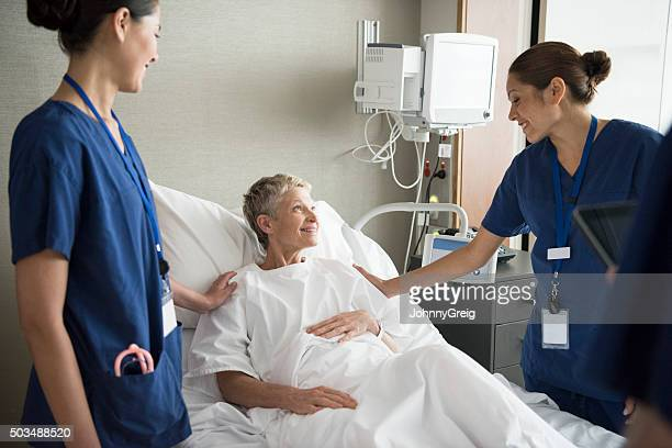 Senior woman in hospital bed with two female nurses, smiling