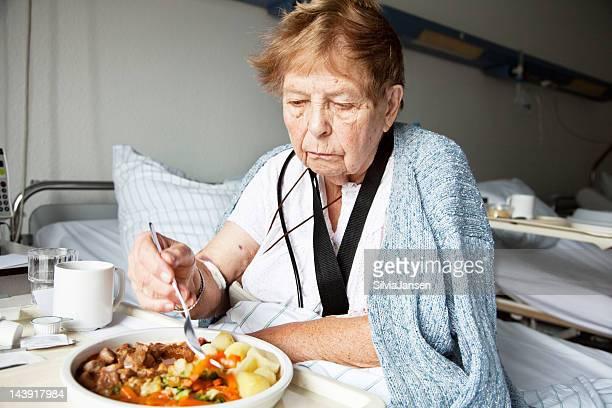 senior woman in hospital eating