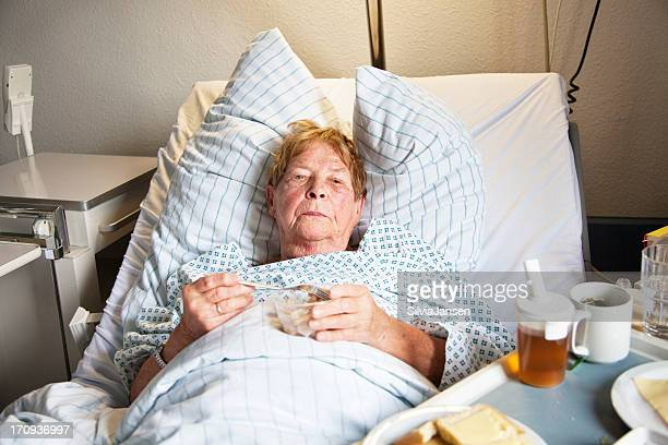 senior woman in hospital eating - old woman in sick bed stock photos and pictures
