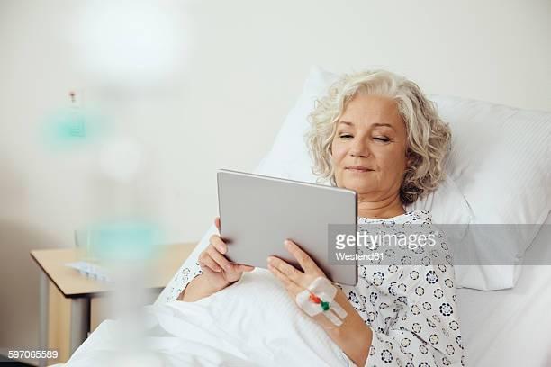 Senior woman in hospital using digital tablet
