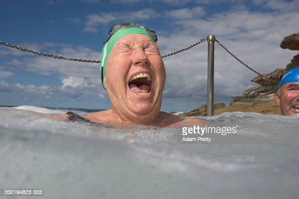 Senior woman in infinity pool, laughing, close-up